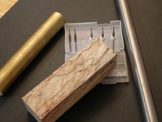 The raw materials, Spalted Hard Maple, o1 drill rod, 360 brass, & micro endmills.